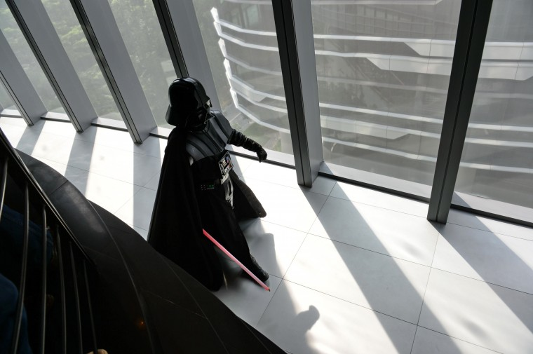 A staff member dressed as the Darth Vader (C) character from George Lucas' Star Wars films arrives for photographers at the opening of Disney's Lucasfilms' new animation production facility, the Sandcrawler in Singapore on January 16, 2014. The award-winning Sandcrawler building was officially opened on January 16, as its regional headquarters for Lucasfilm Singapore. (Roslan Rahman/AFP/Getty Images)
