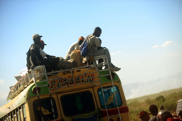 A group of men ride on the roof of a bus while it travels from Titanyen to Port-au-Prince on January 15, 2015. (Hector Retamal/AFP/Getty Images)