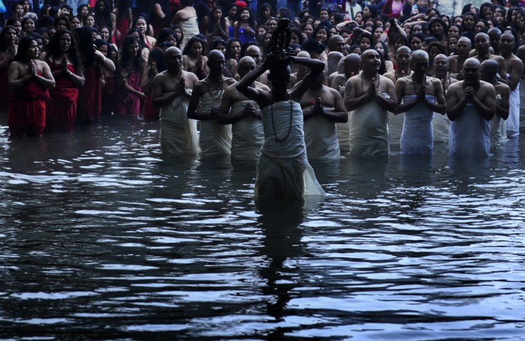 Nepalese Hindu devotees gather to bathe in the Shali River on the outskirts of Kathmandu on January 16, 2014. Hundreds of married and unmarried women in the Himalayan nation have started a month-long fast in the hope of a prosperous life and conjugal happiness. (Prakash Mathema/AFP/Getty Images)
