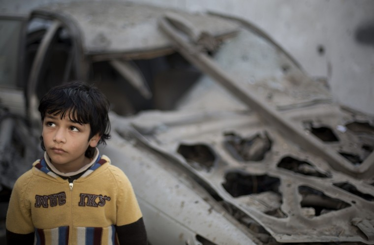 A Palestinian boy stands near a destroyed car following overnight Israeli air strikes in Gaza City on January 16, 2014. Israeli air strikes in the Gaza Strip against training camps used by the armed wing of the territory's Hamas rulers left four children and a woman wounded, Palestinian medical sources said. (Mohammed Abed/AFP/Getty Images)