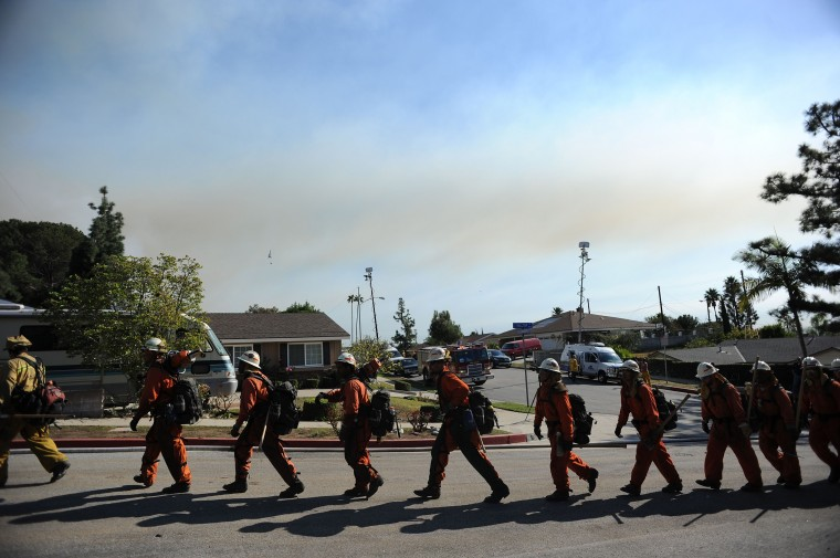 Firefigfhters prepare to attack the Colby Fire on January 16, 2014 in Azusa, California. The fast-moving Colby Fire originated early on Thursday in the San Gabriel Mountains just north of Glendora, about 30 miles (48kms) northeast of Los Angeles. Nearly 900 homes were evacuated Thursday after a wildfire scorched forests near Los Angeles, and cast a plume of smoke over the city, police said. Glendora police detained three men who allegedly set a campfire which sparked the blaze, shortly before 6:00 am (1400 GMT). (Robyn Beck/AFP/Getty Images)