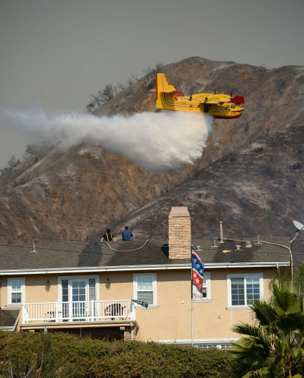 Homeowners watch from a roof as a firefighting aircraft drops water on the Colby Fire, January 16, 2014 in Azusa, California. The fast-moving Colby Fire originated early on Thursday in the San Gabriel Mountains just north of Glendora, about 30 miles (48kms) northeast of Los Angeles. Nearly 900 homes were evacuated Thursday after a wildfire scorched forests near Los Angeles, and cast a plume of smoke over the city, police said. Glendora police detained three men who allegedly set a campfire which sparked the blaze, shortly before 6:00 am (1400 GMT). (Robyn Beck//AFP/Getty Images)
