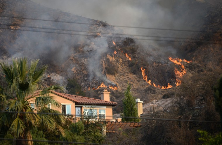 Flames burn near a home during the Colby Fire, January 16, 2014 in Azusa, California. The fast-moving Colby Fire originated early on Thursday in the San Gabriel Mountains just north of Glendora, about 30 miles (48kms) northeast of Los Angeles. Nearly 900 homes were evacuated Thursday after a wildfire scorched forests near Los Angeles, and cast a plume of smoke over the city, police said. Glendora police detained three men who allegedly set a campfire which sparked the blaze, shortly before 6:00 am (1400 GMT). (Robyn Beck/AFP/Getty Images)
