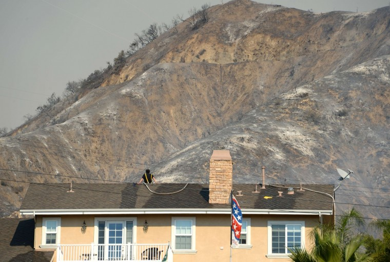 A homeowner keeps watch from his roof during the Colby Fire, January 16, 2014 in Azusa, California. The fast-moving Colby Fire originated early on Thursday in the San Gabriel Mountains just north of Glendora, about 30 miles (48kms) northeast of Los Angeles. Nearly 900 homes were evacuated Thursday after a wildfire scorched forests near Los Angeles, and cast a plume of smoke over the city, police said. Glendora police detained three men who allegedly set a campfire which sparked the blaze, shortly before 6:00 am (1400 GMT). (Robyn Beck/AFP/Getty Images)