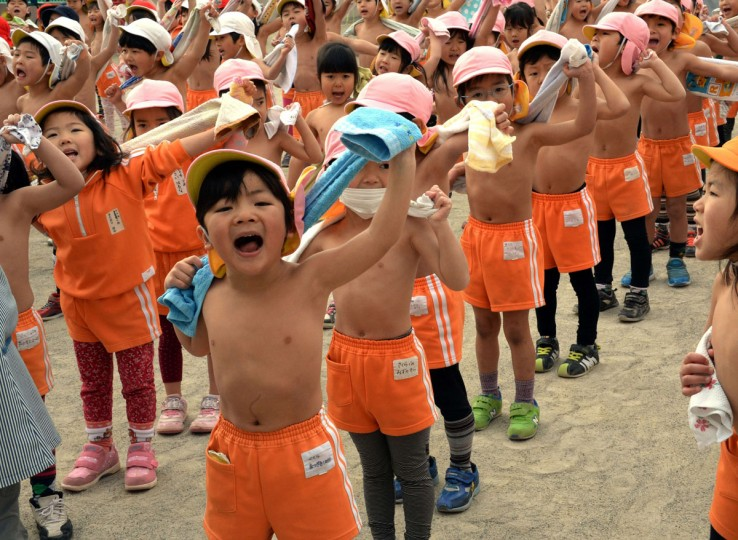 Kindergarten children use towels after a workout in a playground at Tokyo's Mizuho kindergarten on January 20, 2014, on the day of Daikan, which is believed to be Japan's coldest day of the year. (YOSHIKAZU TSUNO/AFP/Getty Images)