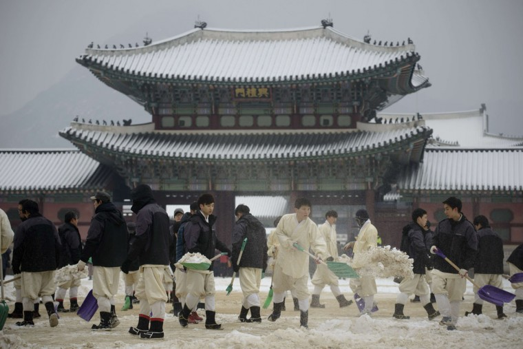 Workers clear snow inside the Gyeongbokgung Palace following overnight snowfall in Seoul on January 20, 2014. January is the coldest month in Seoul, with average temperatures falling some four degrees below freezing. (ED JONES/AFP/Getty Images)