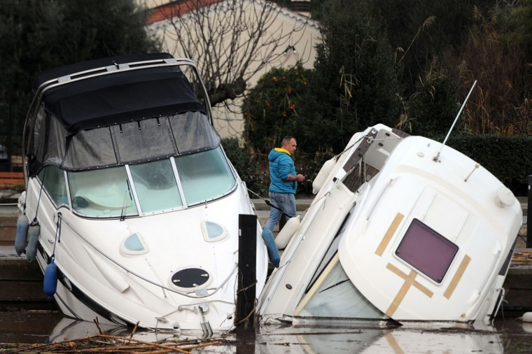 "A man looks at damaged boats in the harbor of La Londe-les-Maures, southeastern France on Januray 20, 2014. River levels were receding early today in southeastern France after ""historic"" floods left two people dead and more than 150 were airlifted to safety. A third man disappeared while out on his boat and 4,000 homes have been left without power after the deluge in the department of Var, they said. (BORIS HORVAT/AFP/Getty Images)"