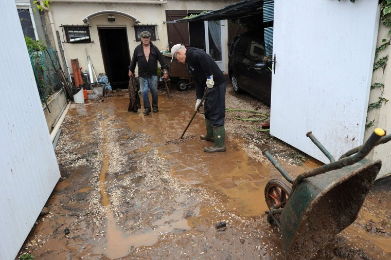 """People clean a house on Januray 20, 2014 in La Londe-les-Maures, southeastern France. River levels were receding early today in southeastern France after """"historic"""" floods left two people dead and more than 150 were airlifted to safety. (BORIS HORVAT/AFP/Getty Images)"""