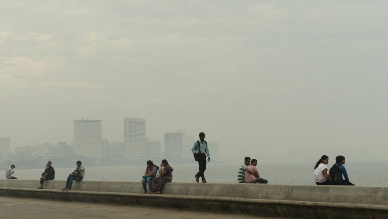 Mumbai residents sit at the sea front on a hazy afternoon in Mumbai on January 20, 2014. (PUNIT PARANJPE/AFP/Getty Images)