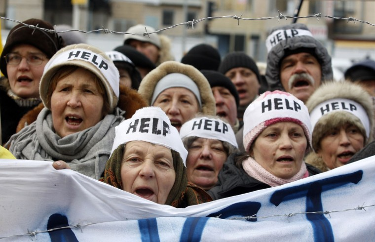"""Protesters wearing headbands reading """"Help"""" shout slogans during an action entitled """"Impose sanctions - stop the violence"""" in front of the European Union delegation in Ukraine in Kiev of January 20, 2014. (YURIY KIRNICHNY/AFP/Getty Images)"""