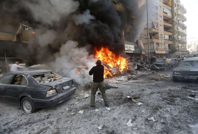 Lebanese men try to extinguish fire from burning cars following an explosion on January 21, 2014 in Haret Hreik, a south Beirut neighbourhood considered a stronghold of the Lebanese Shiite movement Hezbollah. Two people were killed in the apparent suicide car bombing, Lebanon's National News Agency said. (AFP PHOTO/STRSTR/Getty Images)