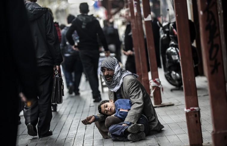 "A Syrian man begs for money with a child at Istiklal Avenue on January 22, 2014 in Istanbul. The United Nations on January 20, 2014 cancelled an invitation to Iran to attend a Syria peace conference this week over its refusal to back calls for a transitional government in Syria, a spokesman said. UN leader Ban Ki-moon is ""deeply disappointed"" at Iran's statements rejecting a communique adopted by international powers on ending the Syria war, said UN spokesman Martin Nesirky. (Bulent Kilic/AFP/Getty Images)"
