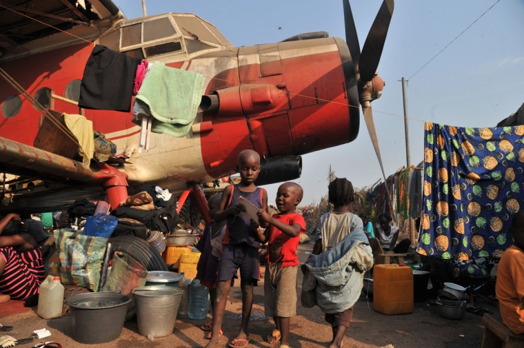 "Children stand next to a plane in the camp for displaced persons at the Mpoko airport in Bangui, on January 21, 2014, a day after the election of Catherine Samba-Panza as the new President of the Central African Republic. The European Union agreed on January 20 to send hundreds of troops to the Central African Republic in a rare joint military mission aimed at ending months of sectarian violence. Saying Europe was ""deeply concerned by the extreme insecurity and instability"" in the impoverished nation, EU foreign ministers gave ""political approval"" to the rapid deployment of a force expected to number between 400 and 600. (Issouf Sanogo/AFP/Getty Images)"