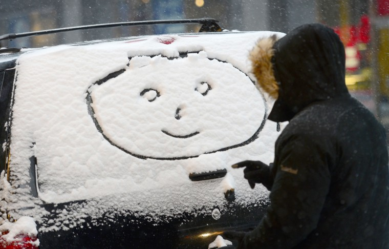 """A person makes a """"happy face"""" on a car window during a snow storm in New York, January 22, 2014. In New York, a storm alert was issue for noon (1700 GMT) Tuesday to 6:00 am (1100 GMT) Wednesday with as much as a foot (30 centimeters) forecast for the metropolitan region. (Emmanuel Dunand/AFP/Getty Images)"""