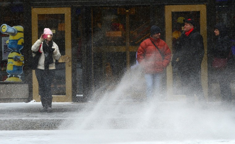 Pedestrians walk during a snow storm in New York, January 22, 2014. In New York, a storm alert was issue for noon (1700 GMT) Tuesday to 6:00 am (1100 GMT) Wednesday with as much as a foot (30 centimeters) forecast for the metropolitan region. (Emmanuel Dunand/AFP/Getty Images)