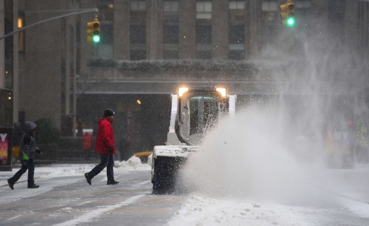 A snow blower clears a path on a pedestrian walk way during a snow storm in New York, January 22, 2014. In New York, a storm alert was issue for noon (1700 GMT) Tuesday to 6:00 am (1100 GMT) Wednesday with as much as a foot (30 centimeters) forecast for the metropolitan region. (Emmanuel Duand/AFP/Getty Images)