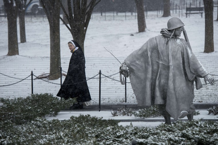 A nun visits the Korean War Memorial January 21, 2014 in Washington, DC. The northeastern United States hunkered down Tuesday for a major snowstorm that forecasters warned could leave as much as one foot (30 centimeters) of snow in some places. Downtown Washington fell virtually silent after the federal government, seeing the swift-moving cold front approaching, closed its doors and told civil servants to stay home. Many offices and schools followed suit, as 20 mile (32 kilometer) per hour winds whipped the falling snow through the unusually quiet streets. Enough snow was expected to fall on the US capital to turn the evening rush hour into a Beltway traffic nightmare, as the storm churned its way into New York and the northeastern New England states.(Brendan Smialowski/AFP/Getty Images)