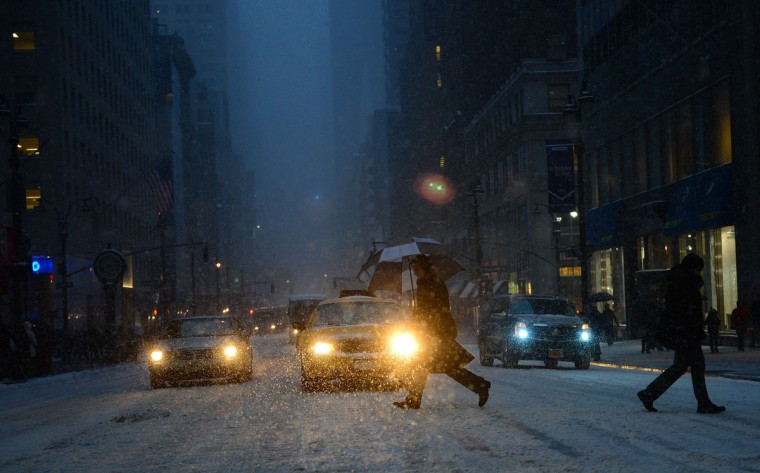 People walk during a snow storm in New York, January 21, 2014. In New York, a storm alert was issue for noon (1700 GMT) Tuesday to 6:00 am (1100 GMT) Wednesday with as much as a foot (30 centimeters) forecast for the metropolitan region. (Emmanuel Duand/AFP/Getty Images)