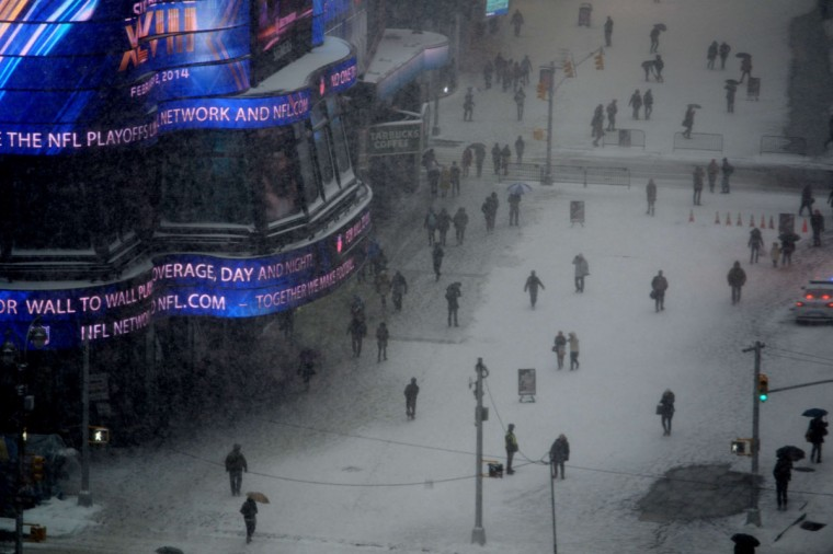 People walk through the pedestrian areas in New York's Times Square as snow falls January 21, 2014. In New York, a storm alert was issue for noon (1700 GMT) Tuesday to 6:00 am (1100 GMT) Wednesday with as much as a foot (30 centimeters) forecast for the metropolitan region. (Stan Honda/AFP/Getty Images)