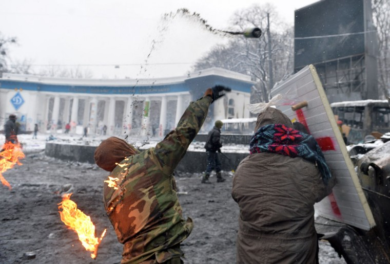 A protesters throws a molotov cocktail at the police during clashes in the center of Kiev on January 22, 2014. Ukrainian police on Wednesday stormed protesters' barricades in Kiev as violent clashes erupted and activists said that one person had been shot dead by the security forces. Total of two activists shot dead during clashing. The move by police increased tensions to a new peak after two months of protests over President Viktor Yanukovych's failure to sign a deal for closer ties with the EU. (Sergei Supinsky/AFP/Getty Images)