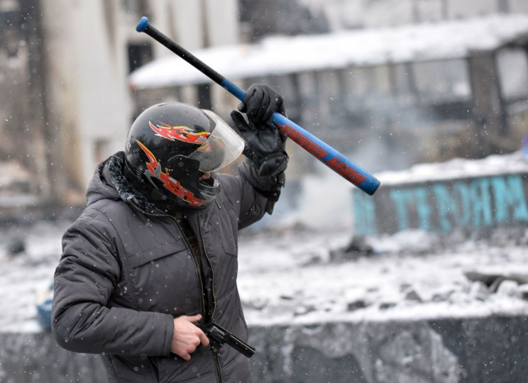 A protester holding a gun and a baseball bat gestures during clashes with the police in the center of Kiev on January 22, 2014. Ukrainian police on Wednesday stormed protesters' barricades in Kiev as violent clashes erupted and activists said that one person had been shot dead by the security forces. Total of two activists shot dead during clashing. The move by police increased tensions to a new peak after two months of protests over President Viktor Yanukovych's failure to sign a deal for closer ties with the EU. (Sergei Supinsky/AFP/Getty Images)