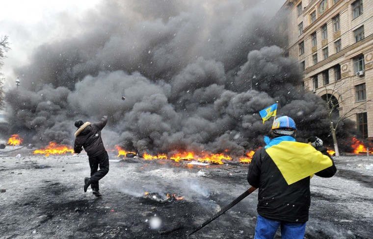Protestors throw stones as they clash with police in the center of Kiev on January 22, 2014. At least two activists were shot dead today as Ukrainian police stormed protesters' barricades in Kiev, the first fatalities in two months of anti-government protests. Pitched battles raged in the centre of the Ukrainian capital as protesters hurled stones at police and the security forces responded with tear gas and rubber bullets. (Genya Savilov/AFP/Getty Images)