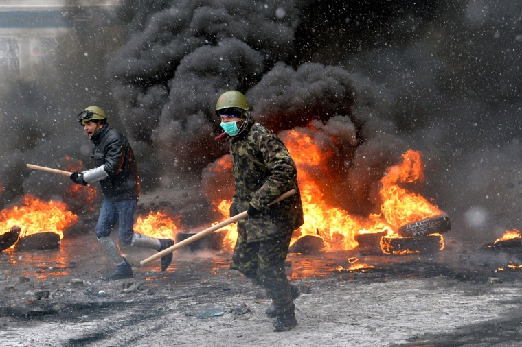 Protestors clash with police in the center of Kiev on January 22, 2014. At least two activists were shot dead today as Ukrainian police stormed protesters' barricades in Kiev, the first fatalities in two months of anti-government protests. Pitched battles raged in the centre of the Ukrainian capital as protesters hurled stones at police and the security forces responded with tear gas and rubber bullets. (Sergei Supinsky/AFP/Getty Images)