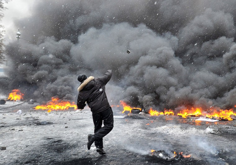 a protestors throws stones as they clash with police in the center of Kiev on January 22, 2014. At least two activists were shot dead today as Ukrainian police stormed protesters' barricades in Kiev, the first fatalities in two months of anti-government protests. Pitched battles raged in the centre of the Ukrainian capital as protesters hurled stones at police and the security forces responded with tear gas and rubber bullets. (Genya Savilov/AFP/Getty Images)