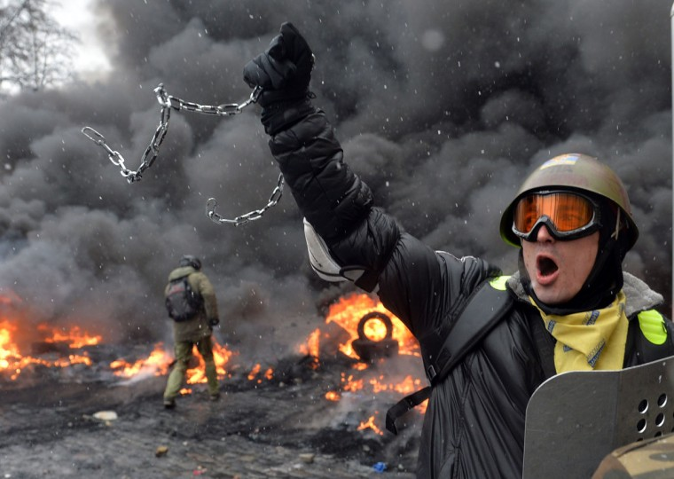 A demonstrator holds up a chain and a riot police shield as protestors clash with police in the center of Kiev on January 22, 2014. At least two activists were shot dead today as Ukrainian police stormed protesters' barricades in Kiev, the first fatalities in two months of anti-government protests. Pitched battles raged in the centre of the Ukrainian capital as protesters hurled stones at police and the security forces responded with tear gas and rubber bullets. (Sergei Supunsky/AFP/Getty Images)