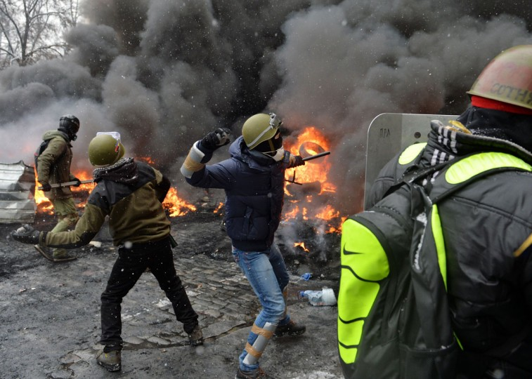 Protestors throw stones as they clash with police in the center of Kiev on January 22, 2014. At least two activists were shot dead today as Ukrainian police stormed protesters' barricades in Kiev, the first fatalities in two months of anti-government protests. Pitched battles raged in the centre of the Ukrainian capital as protesters hurled stones at police and the security forces responded with tear gas and rubber bullets. (Sergei Supinsky/AFP/Getty Images)