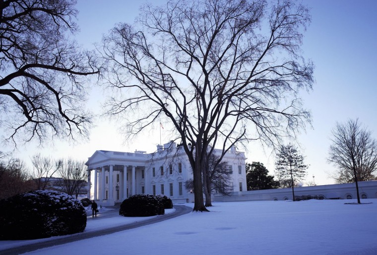 The White House is seen behind a lawn blanketed with snow on January 22, 2014 in Washington, DC. The northeastern US shivered amid heavy snowfall and far below average temperatures Wednesday in a storm that grounded thousands of flights and triggered traffic chaos. (Mandel Ngan/AFP/Getty Images)