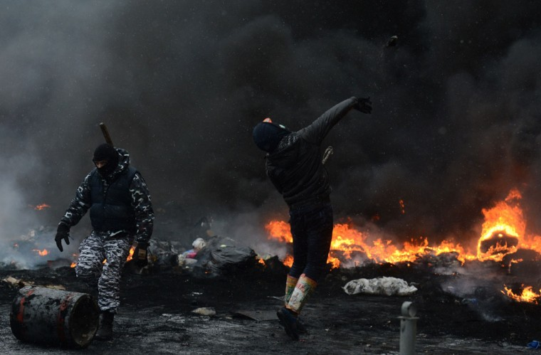 A protestor throws a stone during clashes with riot police in the centre of Kiev on January 22, 2014. Ukrainian police today stormed protesters' barricades in Kiev as violent clashes erupted and activists said that one person had been shot dead by the security forces. Total of two activists shot dead during clashing. The move by police increased tensions to a new peak after two months of protests over President Viktor Yanukovych's failure to sign a deal for closer ties with the EU. (Vasily Maximov/AFP/Getty Images)