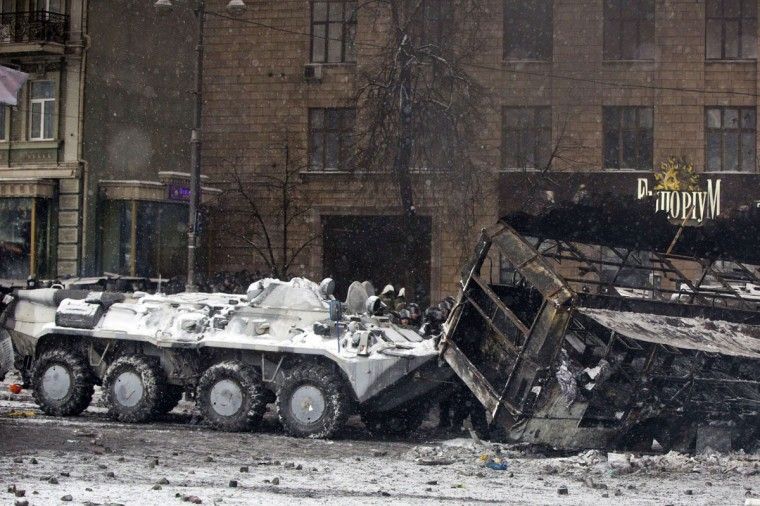 A police armoured personnel carrier moves aside a burned bus during the clashes in the center of Kiev on January 22, 2014. Ukrainian police stormed today protesters' barricades in Kiev as violent clashes erupted and activists said that one person had been shot dead by the security forces. Police for the first time started moving an armoured personnel carrier towards the protesters after storming the barricades. (Yevgeny Feldman/AFP/Getty Images)