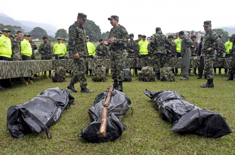 Colombian police officers (front) and soldiers stand by the bodies of Revolutionary Armed Forces of Colombia (FARC) rebels killed in combat, on January 22, 2014, at a military airport in Ibague, department of Tolima, Colombia. Colombian army troops killed at least seven FARC guerrillas in an operation Tuesday in the central department of Tolima, the military said. Military operations this week in different parts of the country have left 26 guerrillas dead, while peace talks continue, installed in November 2012 in Havana, between the Colombian government and the FARC guerrillas, without having been agreed a ceasefire bilateral, Santos believes that it could serve to strengthen the FARC militarily. (Felipe Caicedo/AFP/Getty Images)
