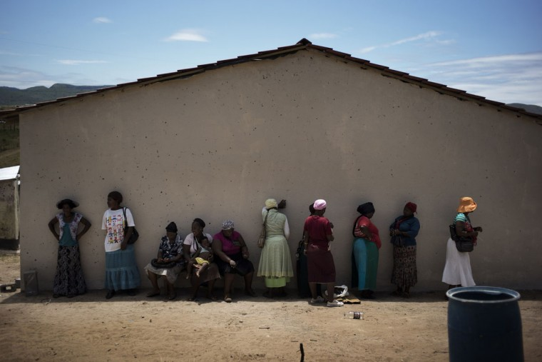 South African Sthandiwe Hlongwane (1st-L) stands with other women outside a newly built house she received from the Economic Freedom Fighters leader and former ANC youth leader Julius Malema in Nkandla on January 22, 2014. The house, a modest concrete building that sits directly opposite the lavish residence of South African President Jacob Zuma in Nkandla, became a gathering spot for those willing to register for the EFF, and where activists meet and listen to the grievances of locals who are disappointed with the ANC. (Marco Longari/AFP/Getty Images)