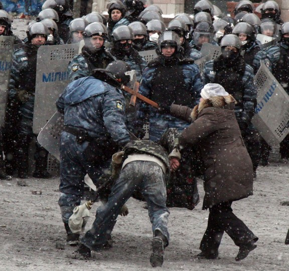 A woman hits a riot police officers with a cross as he pulls a protester during clashes in the center of Kiev on January 22, 2014. Ukrainian police on Wednesday stormed protesters' barricades in Kiev amid violent clashes where two activists were shot dead, the first fatalities in two months of anti-government protests. Pitched battles raged in the centre of the Ukrainian capital as protesters hurled stones and Molotov cocktails at police and the security forces responded with tear gas, stun grenades and rubber bullets. (Anatoliy Stephanov/AFP/Getty Images)