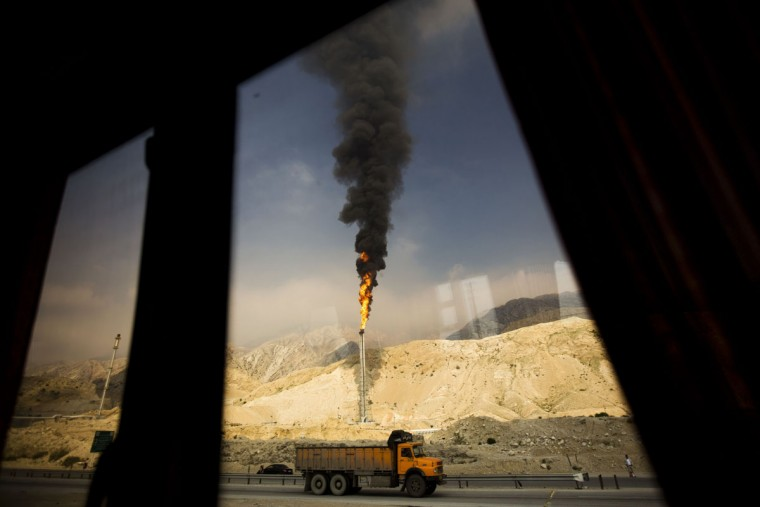 A gas flame is seen through a bus window in the South Pars gas field facilities in the southern Iranian port of Assaluyeh on the shore of the Gulf on January 22, 2014. South Pars, a huge offshore natural gas field shared between Iran and Qatar, holds around 14 trillion cubic metres of gas. (Behrouz Mehri/AFP/Getty Images)