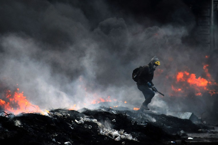 A Ukrainian demonstrator walks past burning tyres and trash set on fire during clashes between pro-EU opposition supporters and riot police in central Kiev on January 23, 2014. Ukraine's opposition agreed to observe an eight-hour truce in clashes with security forces after five days of deadly fighting but threatened to go on the attack if the government failed to agree concessions. (Vasily Maximov/AFP/Getty Images)