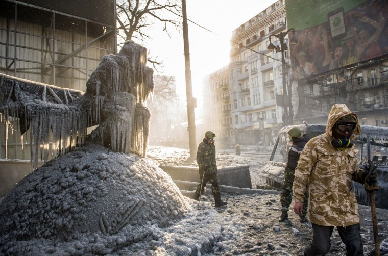 Ukrainian protesters walk past a statue of legendary Ukrainian football coach Valeriy Lobanovsky covered in ice mixed with ash following clashes between riot police and pro-EU protesters in central Kiev on January 23, 2014. Ukraine's opposition agreed to observe an eight-hour truce in clashes with security forces after five days of deadly fighting but threatened to go on the attack if the government failed to agree concessions. Opposition leader and world boxing champion Vitali Klitschko brokered the truce after talks with radical protesters and armoured security forces on the frontline of the clashes, saying the ceasefire should hold while he conducts talks with President Viktor Yanukovych. (Volodymyr Shuvaye/AFP/Getty Images)