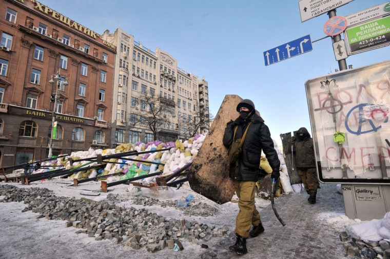 Ukrainian protesters holding makeshift shields and batons walk past a barricade on Krestschatik Street in central Kiev on January 23, 2014. Ukraine's opposition agreed to observe an eight-hour truce in clashes with security forces after five days of deadly fighting but threatened to go on the attack if the government failed to agree concessions. Opposition leader and world boxing champion Vitali Klitschko brokered the truce after talks with radical protesters and armoured security forces on the frontline of the clashes, saying the ceasefire should hold while he conducts talks with President Viktor Yanukovych. (Genya Savilov/AFP/Getty Images)