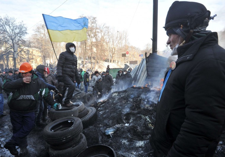 Ukrainian protesters stand next to a burning pile of tyres set on fire during clashes between pro-EU demonstrators and riot police in Kiev on January 23, 2014. Ukraine's opposition agreed to observe an eight-hour truce in clashes with security forces after five days of deadly fighting but threatened to go on the attack if the government failed to agree concessions. Opposition leader and world boxing champion Vitali Klitschko brokered the truce after talks with radical protesters and armoured security forces on the frontline of the clashes, saying the ceasefire should hold while he conducts talks with President Viktor Yanukovych. (Genya Savilov/AFP/Getty Images)