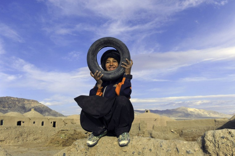 An Afghan child plays in the outskirts of Herat on January 23, 2014. Economic development is considered a vital weapon to stop the country from sinking back into civil war and to stem Islamist extremism after 100,000 international combat troops pull out. (Aref Karimia/AFP/Getty Images)