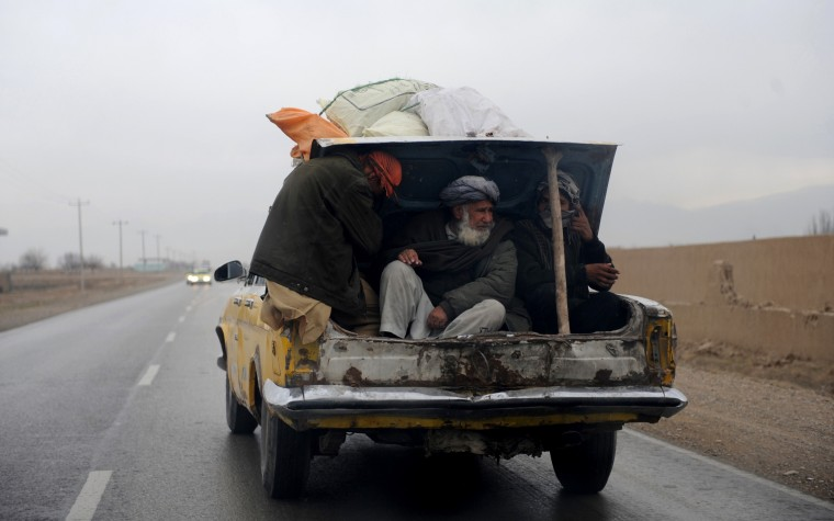 Afghan men ride in the trunk of a car in Mazar-i-Sharif on January 24, 2014. Economic development is considered a vital weapon to stop the country from sinking back into civil war and to stem Islamist extremism after 100,000 international combat troops pull out next year. (Farshad Usyan/AFP/Getty Images)