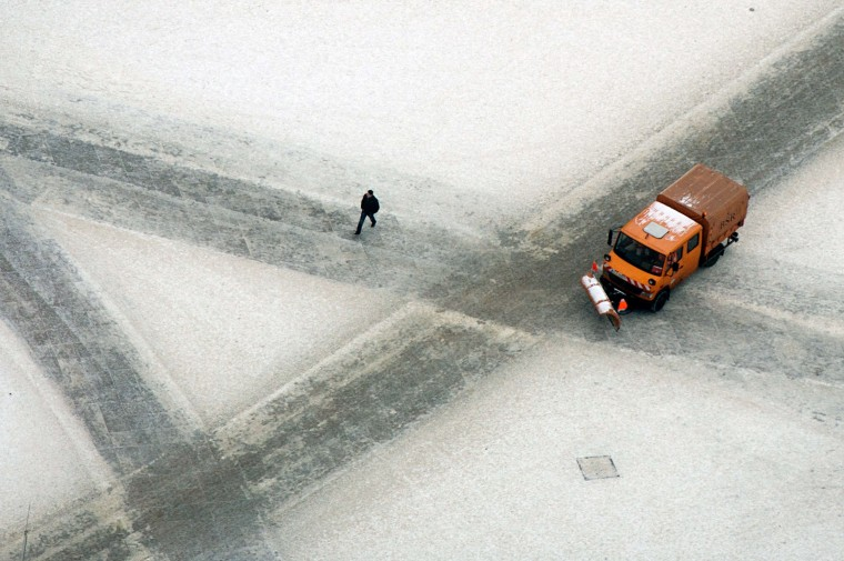 A car drives on a snowy road on January 24, 2014 in Berlin. (Maurizio Gambarini/AFP/Getty Images)
