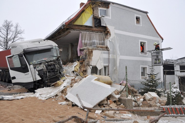 Firemen work in a damaged house after a truck driver lost control of his vehicle on an icy road and crashed into the house on January 24, 2014 in Ostritz, eastern Germany. The building risks to collapse following the accident. (Danilo Dittrich/AFP/Getty Images)