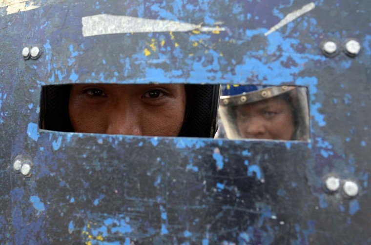 "Anti-riot policemen peer from behind a metal shield during the demolition of ""informal settlers"" houses in Manila on January 27, 2014. Hundreds of ""informal settlers"" houses were demolished by local government authorities to make way for a commercial development. (ted Aljibeted//AFP/Getty Images )"