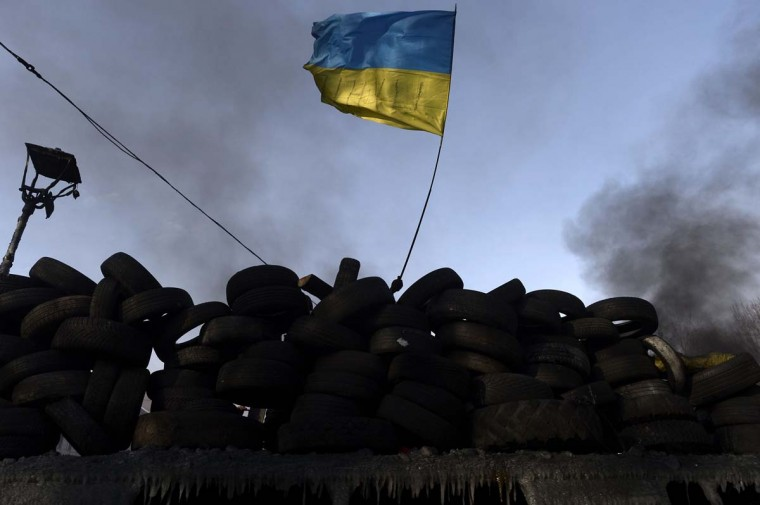 An anti-government protester waves an Ukranian flag behind a road block in Kiev on January 27, 2014. A Ukrainian government minister on January 27 warned protesters that a state of emergency could be imposed to deal with the country's deadly crisis, after radicals seized the justice ministry in Kiev.(Aris Messinis/AFP/Getty Images)