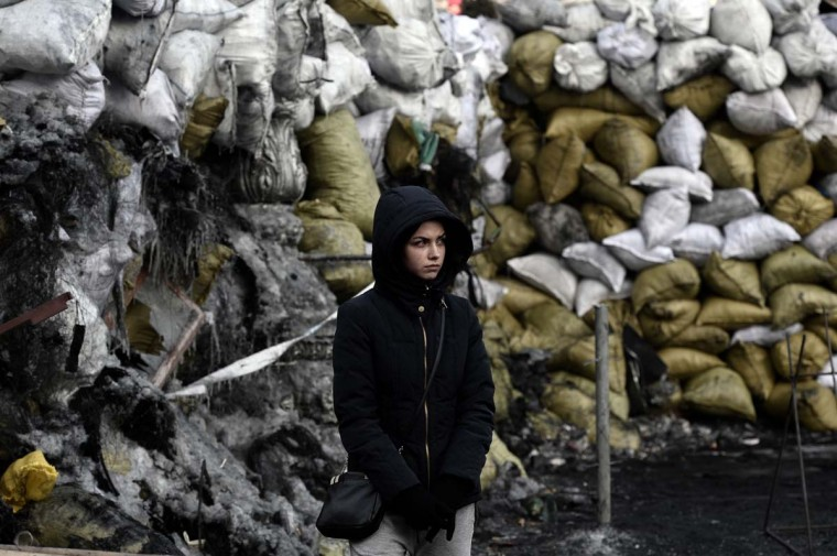 A young woman stands at a road block in Kiev on January 27, 2014. A Ukrainian government minister on January 27 warned protesters that a state of emergency could be imposed to deal with the country's deadly crisis, after radicals seized the justice ministry in Kiev. (Aris Messinis/AFP/Getty Images)