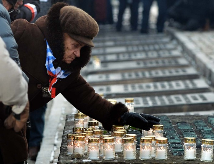 A survivor puts down a candle during a ceremony in the former Nazi concentration camp Auschwitz-Birkenau in Oswiecim, Poland, on Holocaust Day, January 27, 2014. The ceremony took place 69 years after the liberation of the death camp by Soviet troops, in rememberance of the victims of the Holocaust. (Janek Skarzynski//AFP/Getty Images)
