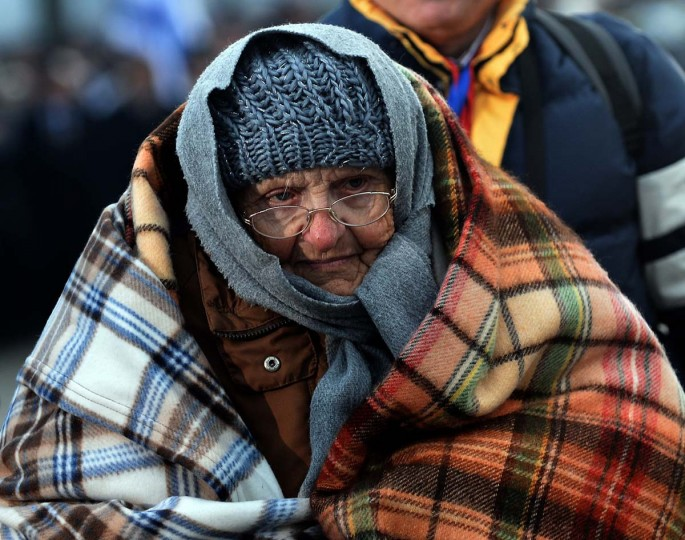 A survivor huddles in a blanket to stay warm during a ceremony in the former Nazi concentration camp Auschwitz-Birkenau in Oswiecim, Poland, on Holocaust Day, January 27, 2014. The ceremony took place 69 years after the liberation of the death camp by Soviet troops, in rememberance of the victims of the Holocaust. (Janek Skarzynski//AFP/Getty Images)
